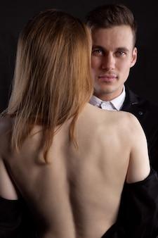 Un bel homme en arrière-plan et une femme nue sexy debout avec son dos