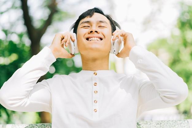 Bel homme asiatique appréciant la musique dans le parc