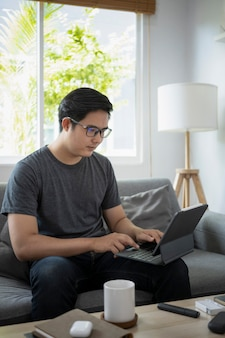Bel homme asiatique assis sur un canapé et travaillant en ligne avec une tablette informatique.