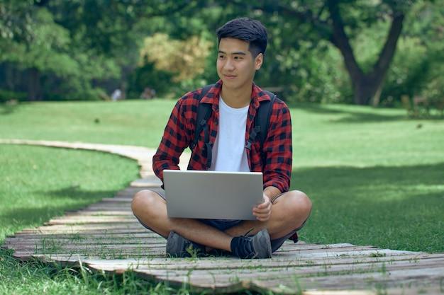 Bel homme asiatique assis dans un jardin à l'aide d'un ordinateur portable