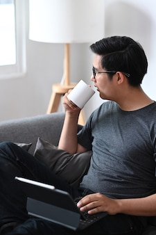 Bel homme asiatique buvant du café et utilisant une tablette informatique sur un canapé.