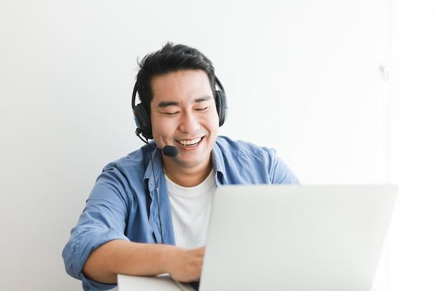 Bel homme asiatique en chemise bleue à l'aide d'un ordinateur portable avec casque parler sourire et visage heureux