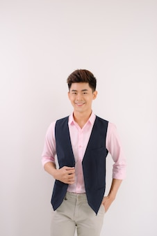 Bel homme asiatique debout et sourire posant sur fond gris