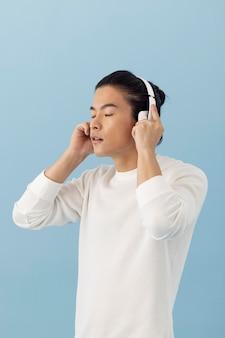 Bel homme asiatique écoutant de la musique avec des écouteurs