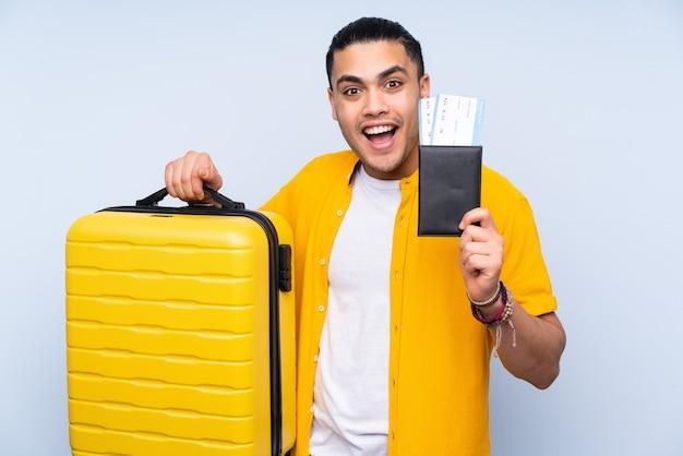 Bel homme asiatique isolé sur fond bleu en vacances avec valise et passeport et surpris