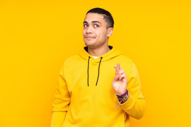 Bel homme asiatique isolé sur fond jaune maintient la paume ensemble. la personne demande quelque chose