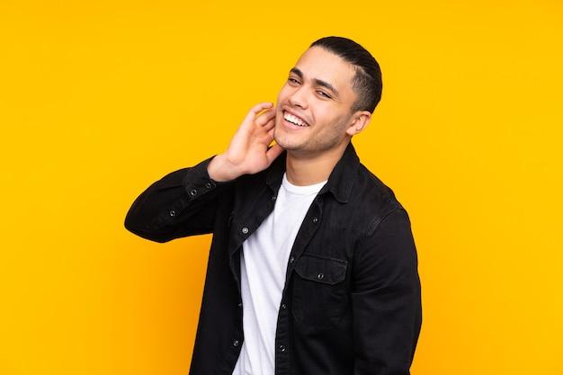 Bel homme asiatique isolé sur un mur jaune pointant vers l'avant avec une expression heureuse