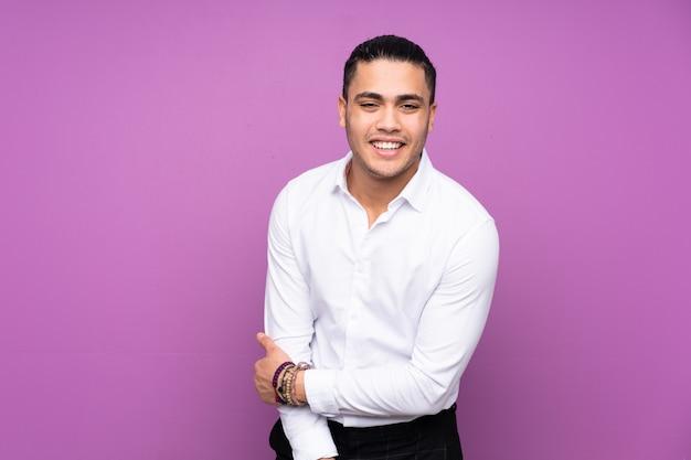 Bel homme asiatique sur le mur bleu en riant