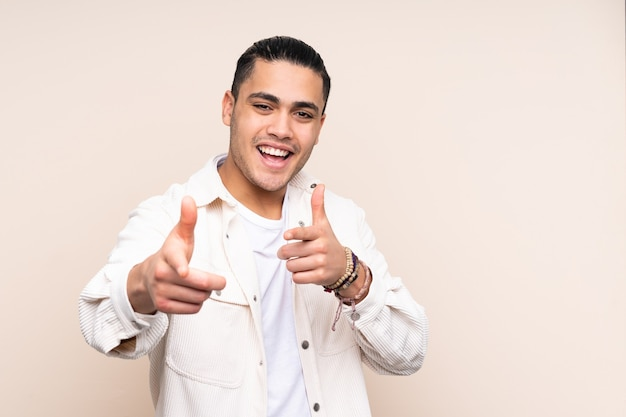 Bel homme asiatique sur mur isolé pointant vers l'avant et souriant