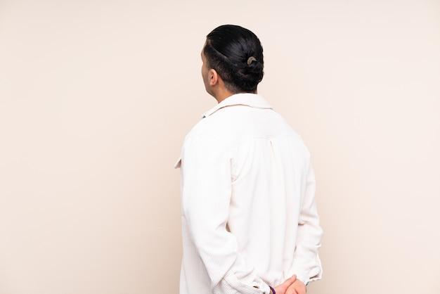 Bel homme asiatique sur mur en position arrière et regardant en arrière
