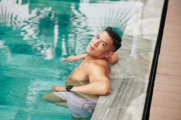 Bel homme asiatique musclé se détendre dans la piscine par une chaude journée