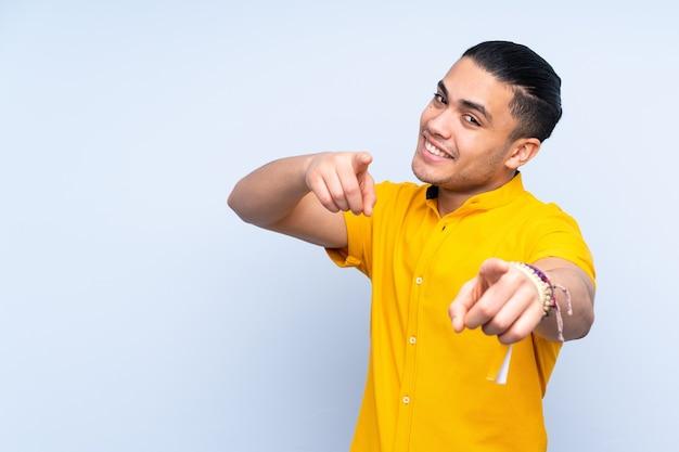 Bel homme asiatique pointant vers l'avant avec une expression heureuse