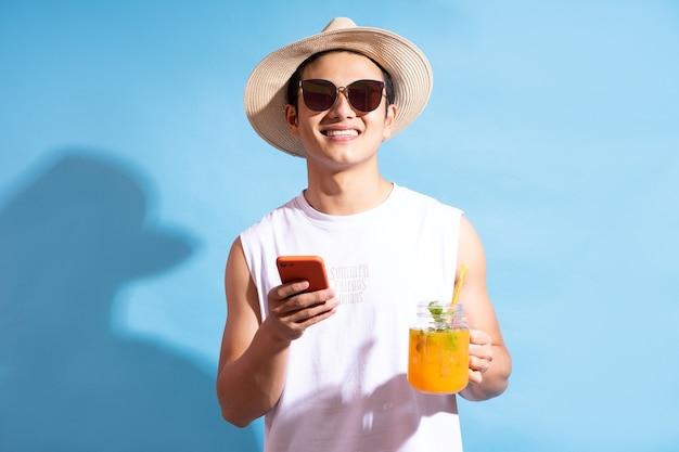 Bel homme asiatique portant des lunettes de soleil tenant un cocktail à la main et à l'aide de téléphone
