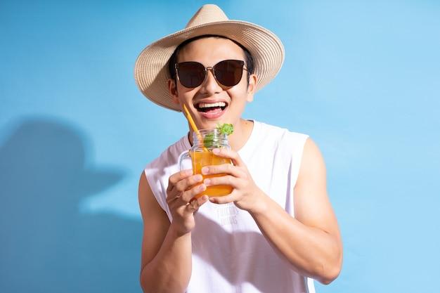 Bel homme asiatique portant des lunettes de soleil tenant un cocktail à la main