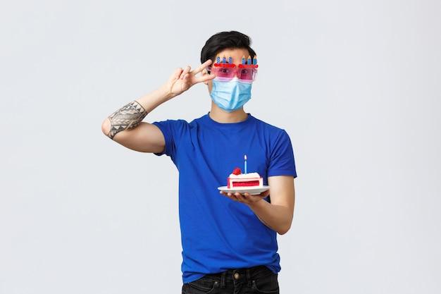 Bel homme asiatique portant un masque de protection avec un gâteau d'anniversaire