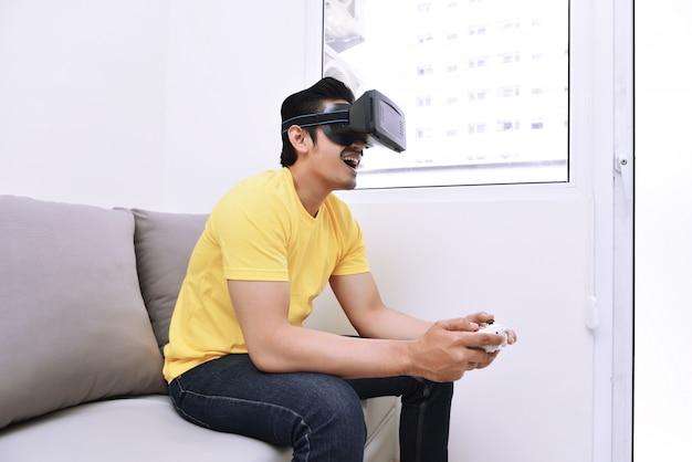 Bel homme asiatique portant la réalité virtuelle tout en jouant à des jeux vidéo