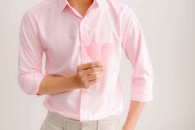 Bel homme asiatique tenant du papier coeur rose posant sur fond gris