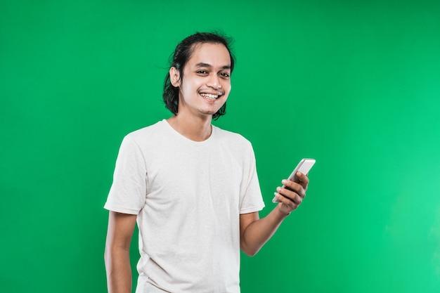Bel homme asiatique tenant handphone avec expression de sourire bonheur tout en regardant la caméra isolée sur fond vert
