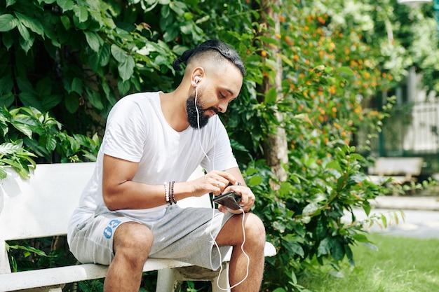 Bel homme assis sur un banc dans le parc, écoutant de la musique sur smartphone et vérifiant la smartwatch