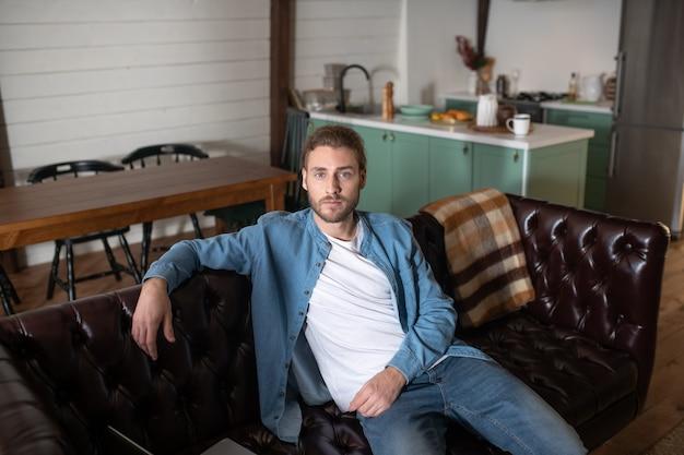 Un bel homme assis sur le canapé en cuir