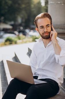Bel homme assis dans les escaliers et travaillant sur ordinateur