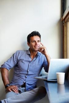 Bel homme assis avec un ordinateur portable au café