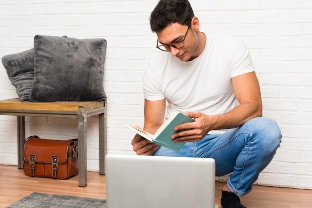 Bel homme assis sur le sol avec son ordinateur portable