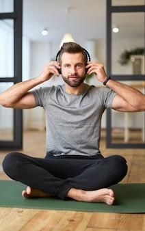 Bel homme assis sur un tapis de yoga et mettant des écouteurs sans fil