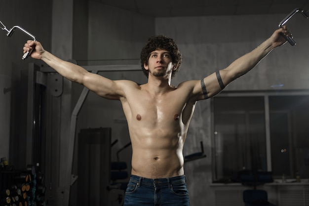 Bel homme athlétique entraîne sa poitrine dans la salle de gym