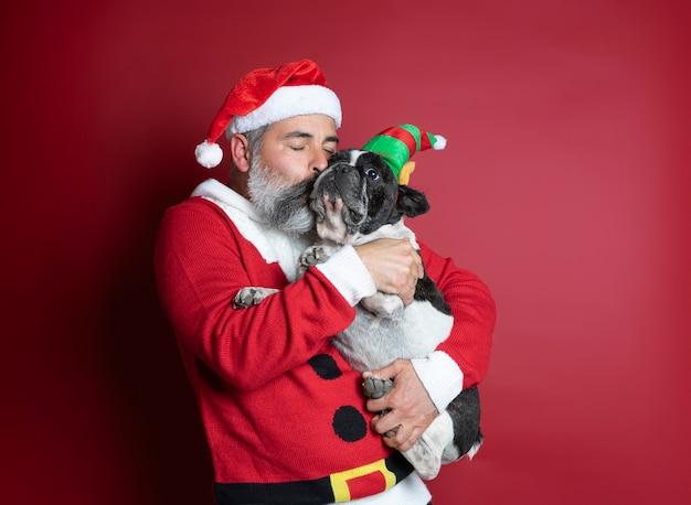 Bel homme au chapeau de noël et pull serrant son chien habillé pour noël sur le rouge
