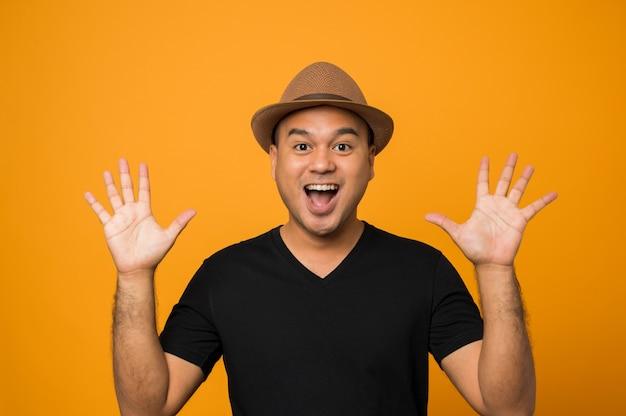 Bel homme au chapeau portant des vêtements décontractés montrant deux paumes, donnant cinq gestes élevés