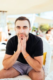Bel homme au repos au restaurant de plage en bord de mer. .