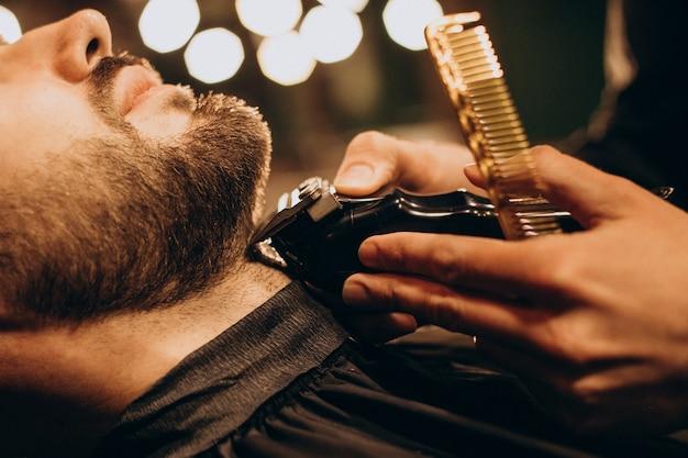 Bel homme au salon de coiffure barbe de rasage
