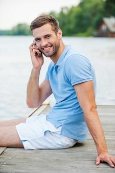 Bel homme au téléphone. vue latérale du beau jeune homme parlant au téléphone portable et souriant alors qu'il était assis au bord de la rivière