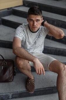 Bel homme aux beaux yeux gris avec une coiffure élégante dans un t-shirt à la mode en short à la mode avec un sac en cuir