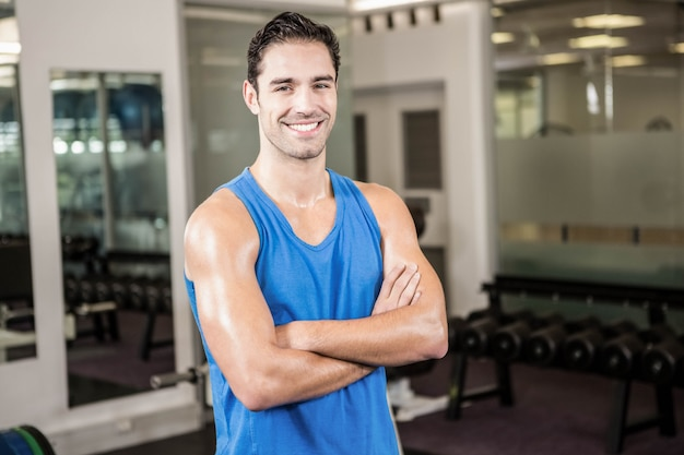 Bel homme aux bras croisés en regardant la caméra dans la salle de gym