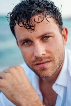 Bel homme aux cheveux mouillés au bord de la mer