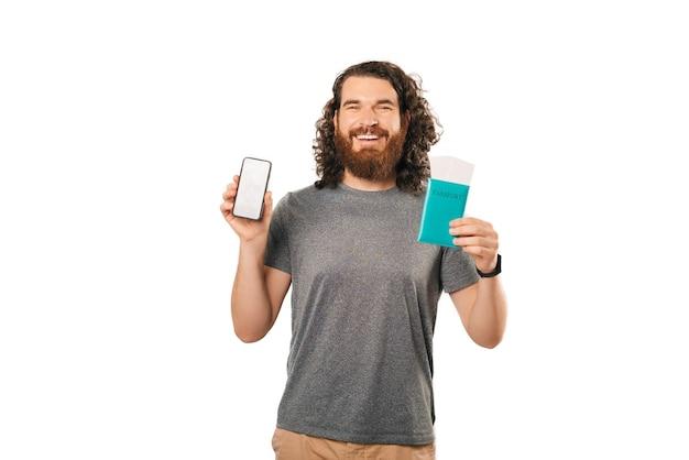 Bel homme aux cheveux ondulés tient un téléphone et un passeport sur fond blanc.