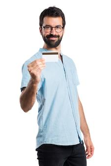 Bel homme aux lunettes bleues tenant une carte de crédit