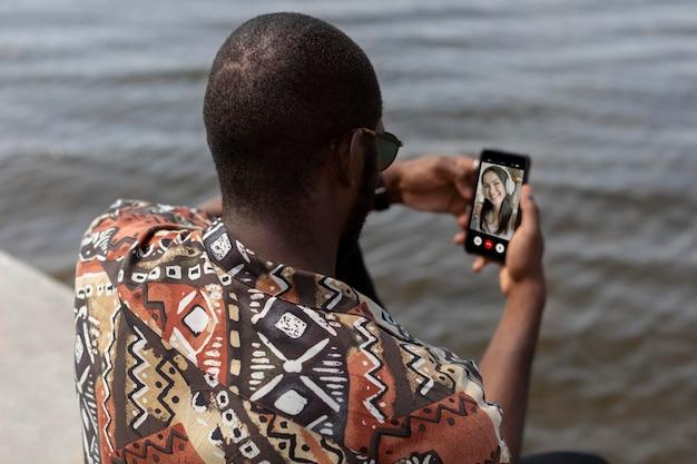 Bel homme ayant un appel vidéo avec un smartphone moderne à l'extérieur