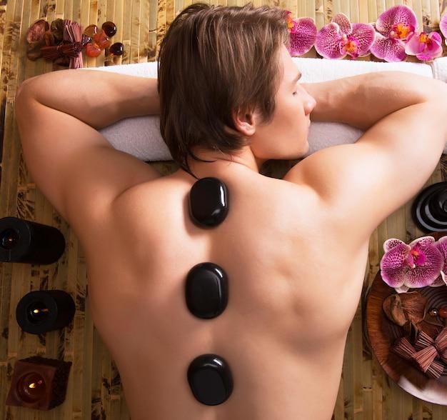 Bel homme ayant un massage aux pierres dans un salon de spa. mode de vie sain.