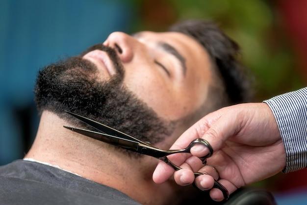 Bel homme ayant un rasage avec des ciseaux au salon de coiffure.