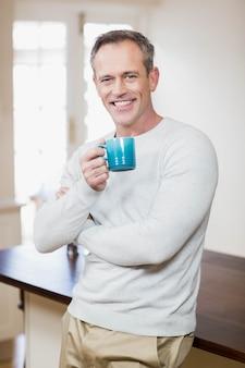 Bel homme ayant une tasse de café dans la cuisine