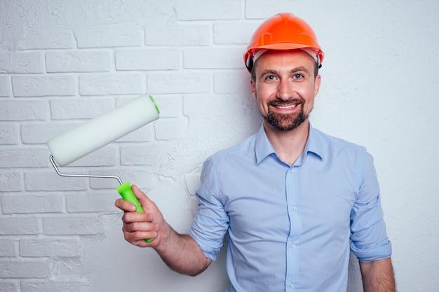 Un bel homme avec une barbe et un casque de protection sur fond de mur de briques blanches tient une brosse à rouleau.