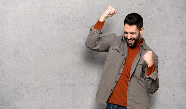 Bel homme à la barbe célébrant une victoire sur un mur texturé