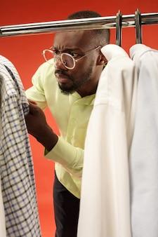 Bel homme avec barbe en choisissant une chemise dans un magasin