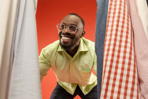 Bel homme avec barbe choisissant chemise dans un magasin