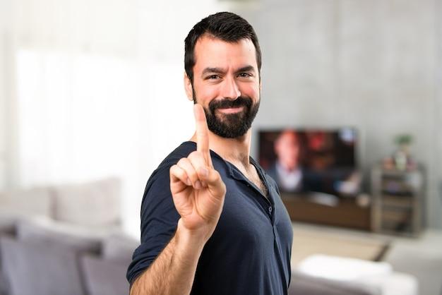 Bel homme avec barbe comptant un intérieur de la maison
