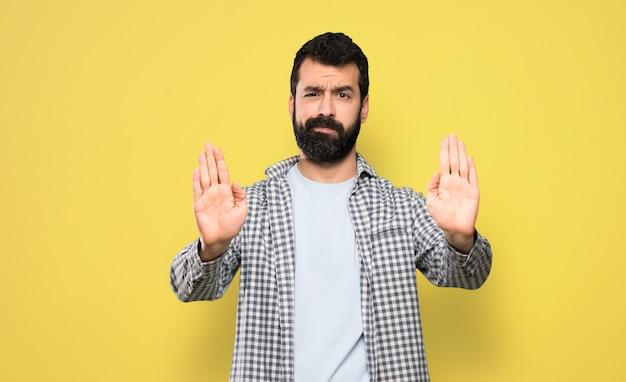 Bel homme à la barbe faisant un geste d'arrêt et déçu