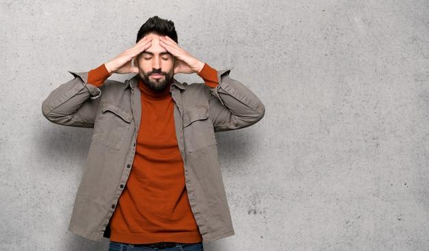 Bel homme à la barbe malheureux et frustré avec quelque chose sur le mur texturé